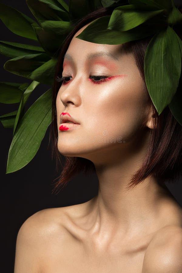 Belle fille asiatique avec un art lumineux de maquillage dans des feuilles vertes Visage de beauté Image créatrice photos stock