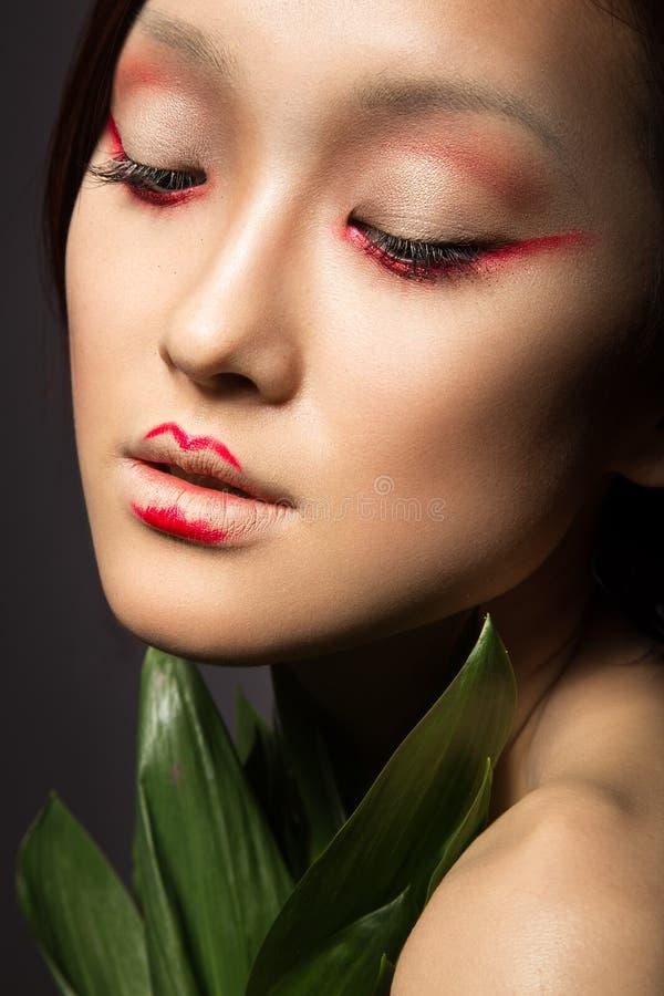 Belle fille asiatique avec un art lumineux de maquillage dans des feuilles vertes Visage de beauté Image créatrice photo libre de droits