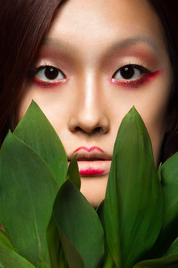 Belle fille asiatique avec un art lumineux de maquillage dedans photo libre de droits