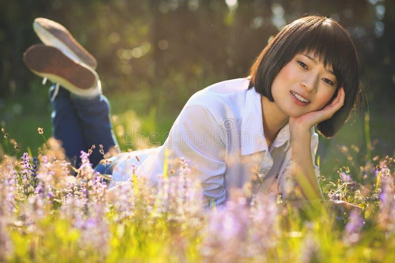 Belle fille asiatique détendant parmi des fleurs photos stock