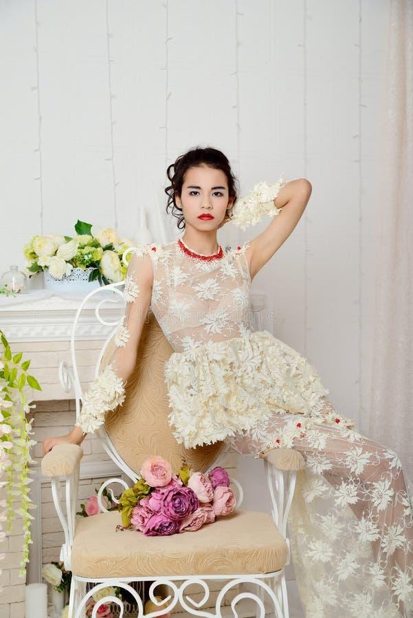 Belle fille asiatique dans les sous-vêtements posant dans le studio sur une chaise de vintage avec un bouquet des fleurs et regar photo libre de droits