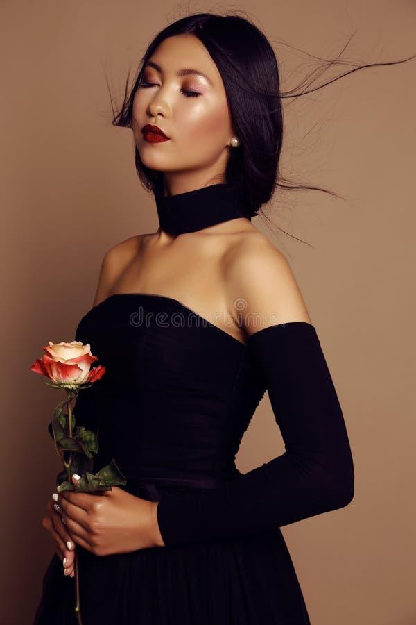 Belle fille asiatique de regard avec les cheveux noirs portant la robe élégante photos libres de droits