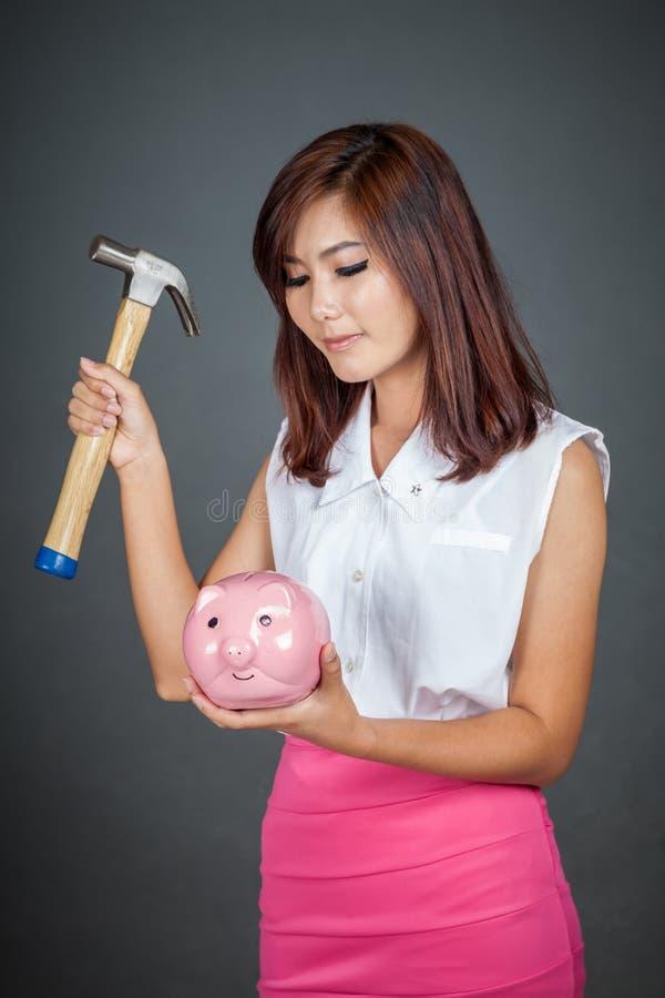 Belle fille asiatique environ pour frapper la tirelire avec le marteau photos libres de droits