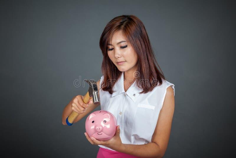 Belle fille asiatique environ pour frapper la tirelire avec le marteau photographie stock libre de droits