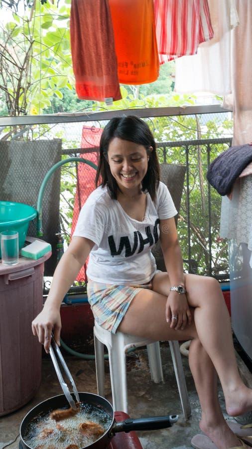 Belle fille asiatique faisant cuire dehors, jour, faisant frire en nourriture de wok photo stock