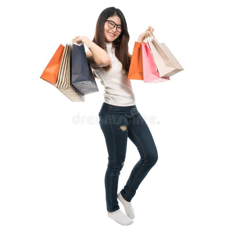 Belle fille asiatique tenant des paniers sur les deux mains, d'isolement sur le fond blanc, le mode de vie ou le concept shopahol photographie stock libre de droits