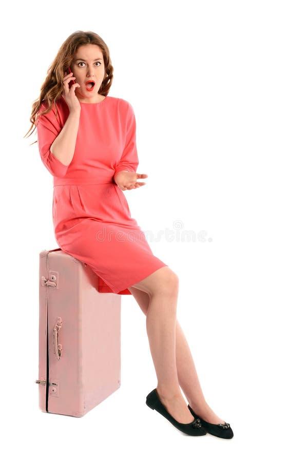 Belle fille assise sur la valise parlant au téléphone portable, d'isolement sur le blanc photo libre de droits