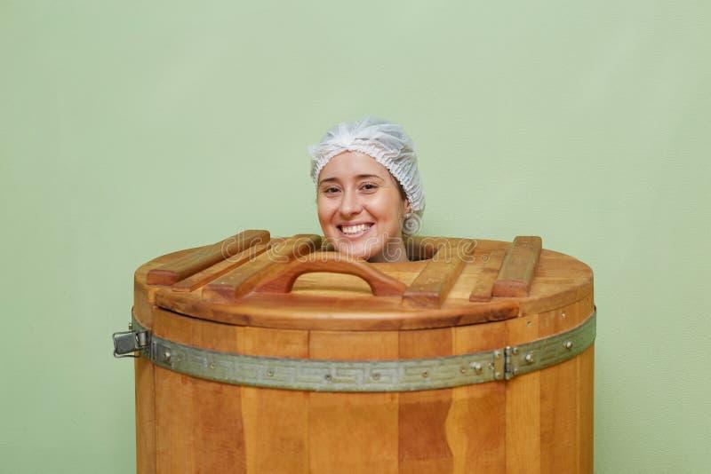 Belle fille au centre de station thermale Phyto sauna de baril de cèdre photographie stock libre de droits