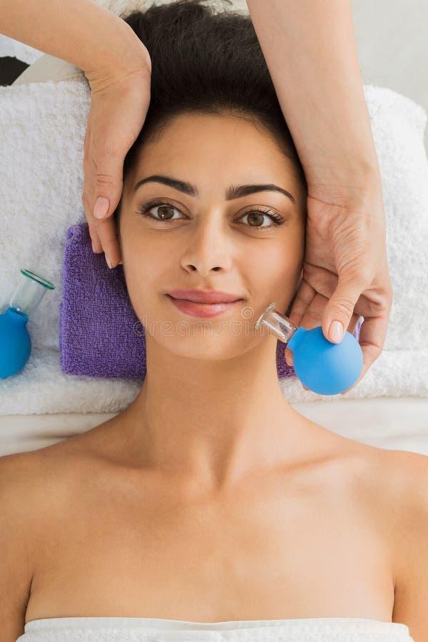 Belle fille au massage mettant en forme de tasse au centre de bien-être de station thermale photo stock