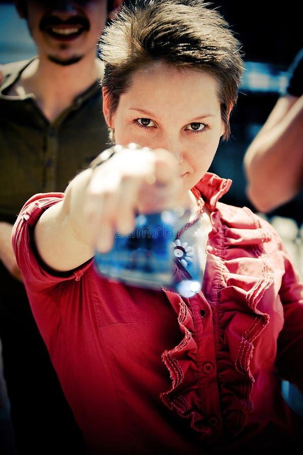 Belle fille au pointage rouge à l'appareil-photo photographie stock