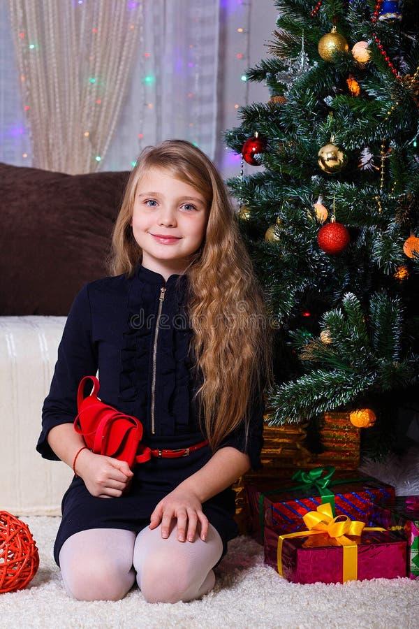 Belle fille aux cheveux blancs caucasienne posant près de la cheminée, de l'humeur de Noël et de nouvelle année image stock