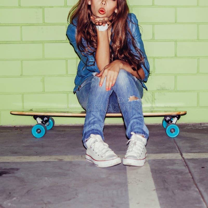 Belle fille aux cheveux longs avec une planche à roulettes en bois près d'un vert photos stock