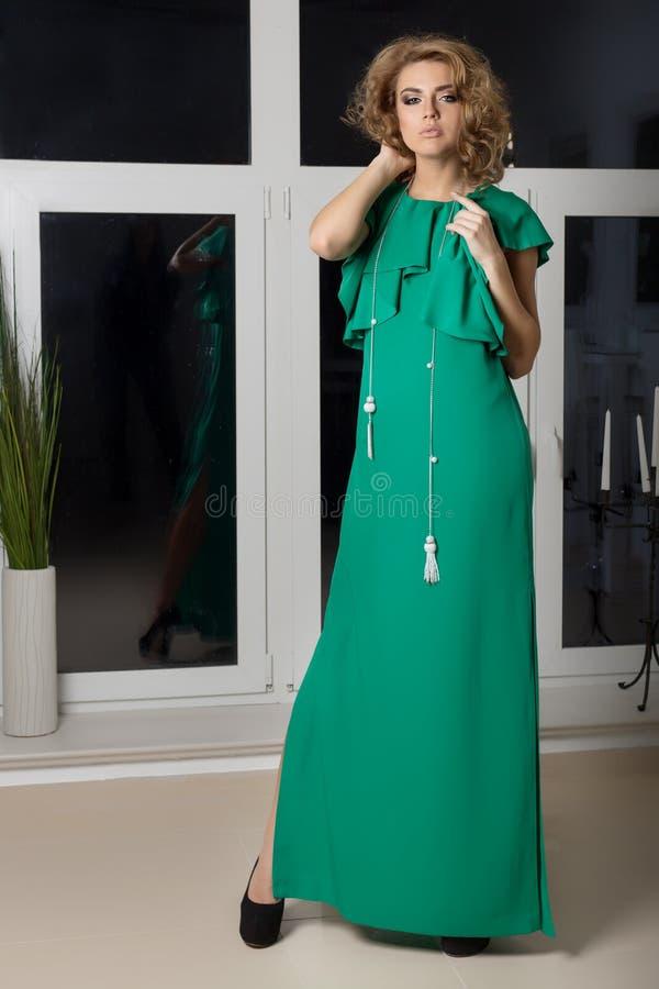 Belle fille aux jambes longues élégante sexy dans une robe de soirée de long vert avec la coiffure de soirée et le maquillage lum images stock