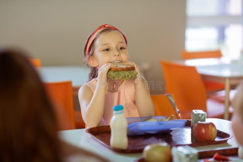 Belle fille aux yeux noirs mordant son sandwich avec de la laitue photo stock