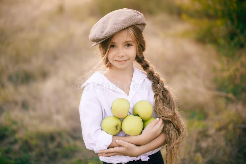Belle fille avec de longs cheveux blonds tressés dans une tresse dans un chapeau et des pommes dans la campagne photographie stock libre de droits