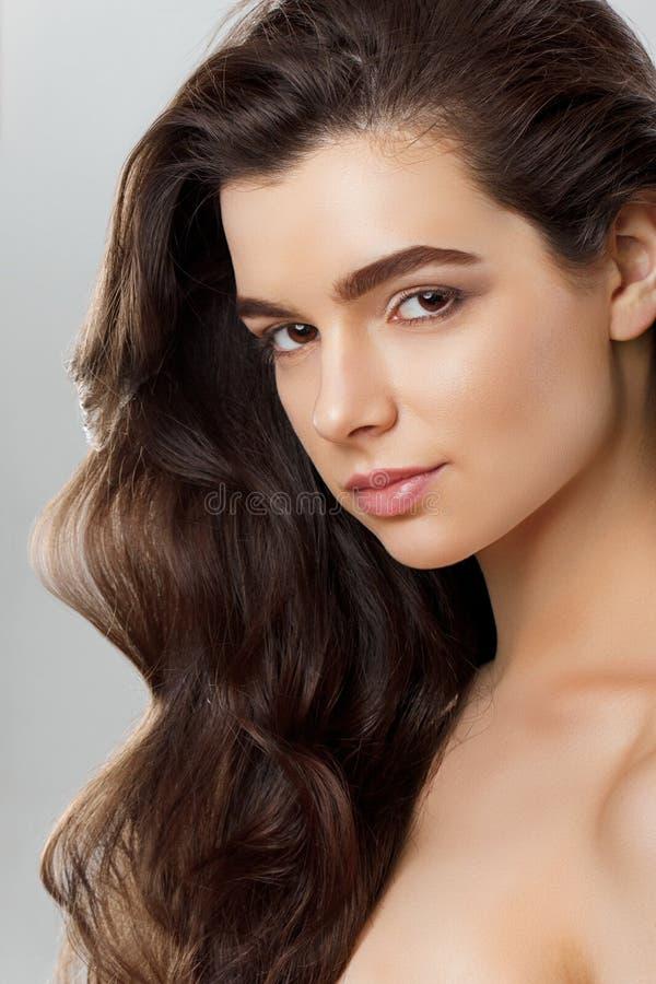Belle fille avec de longs cheveux onduleux et brillants Femme de brune avec la coiffure boucl?e image stock