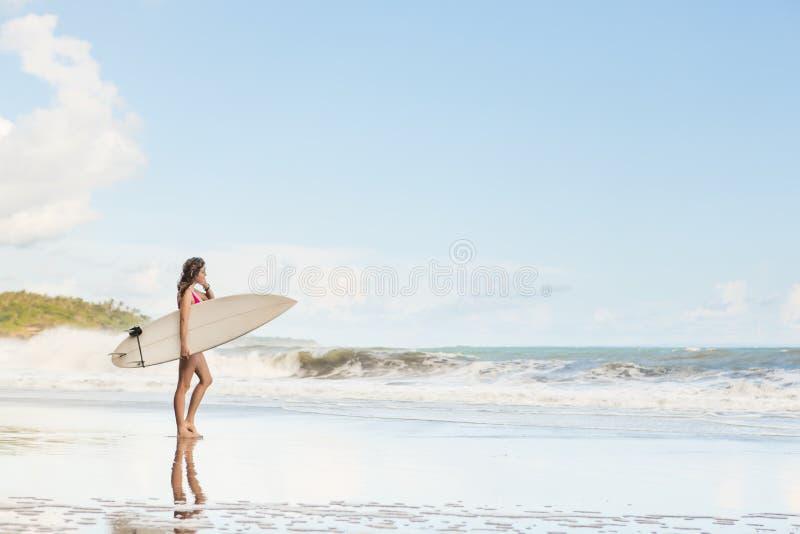 Belle fille avec de longs cheveux sur la plage avec la planche de surf image libre de droits
