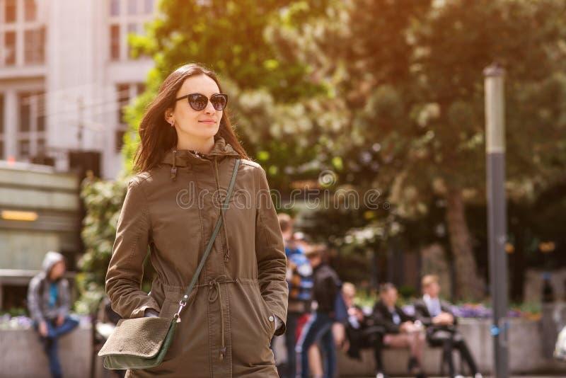 Belle fille avec de longs cheveux utilisant les lunettes de soleil élégantes, vêtements sport et tenant le petit sac Style de vie photo stock