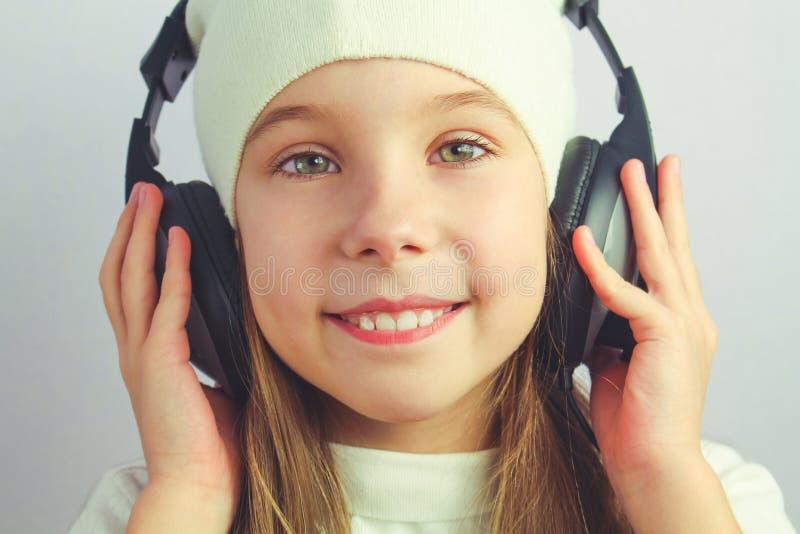 Belle fille avec des écouteurs photographie stock libre de droits