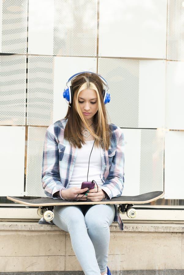 Belle fille avec des écouteurs et la musique de écoute de téléphone intelligent photo libre de droits