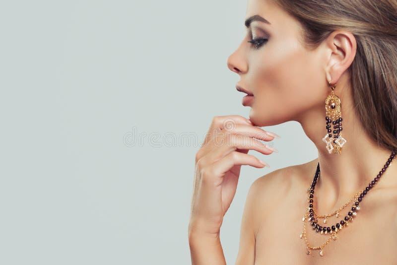 Belle fille avec des boucles d'oreille d'or sur le fond gris image stock