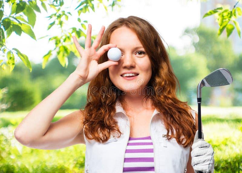 Belle fille avec des cheveux rouges et une boule de golf image libre de droits