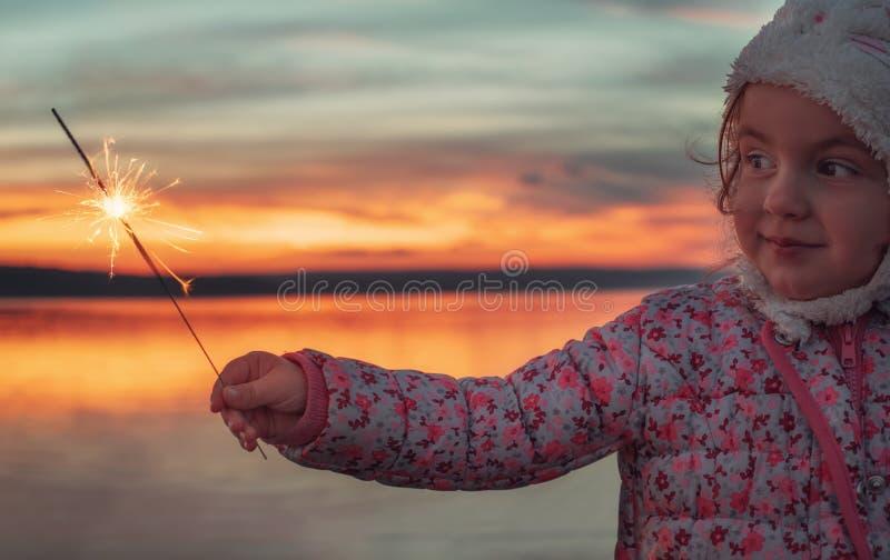 Belle fille avec des cierges magiques sur le lac au coucher du soleil images stock