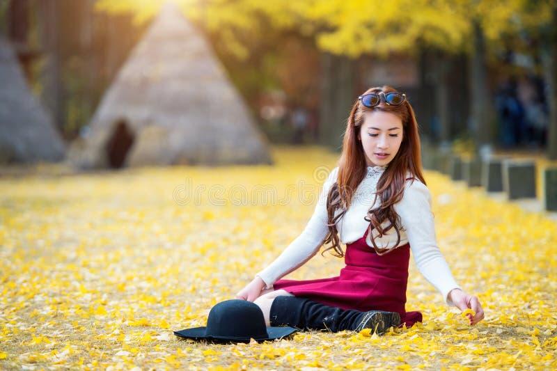 Belle fille avec des feuilles de jaune en Nami Island photo stock