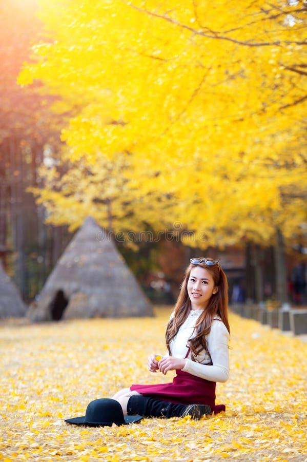 Belle fille avec des feuilles de jaune en Nami Island, Corée image stock
