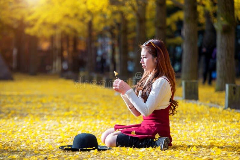 Belle fille avec des feuilles de jaune en Nami Island, Corée photographie stock libre de droits