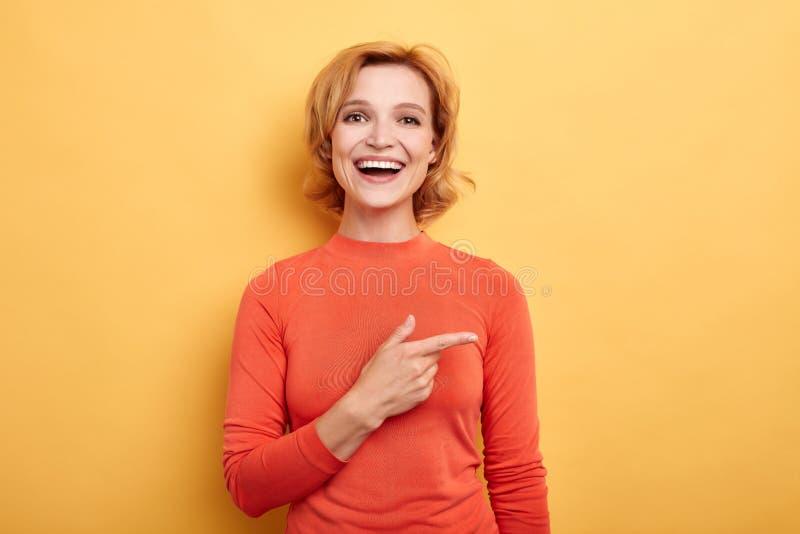 Belle fille avec du charme gaie faisant des gestes le copyspace avec l'index photos libres de droits