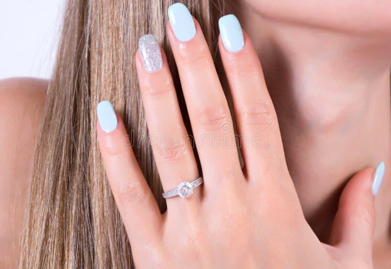 Belle fille avec l'anneau bleu de manucure de vernis à ongles et de mariage de fiançailles de diamants sur le doigt images libres de droits