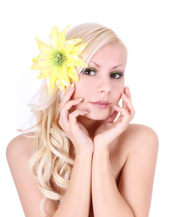 Belle fille avec la fleur jaune dans le cheveu photographie stock libre de droits