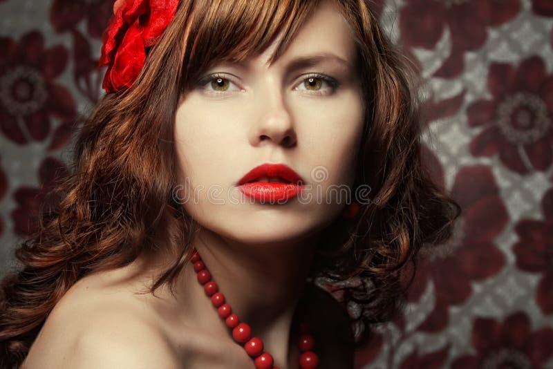 Belle fille avec la fleur rouge dans le cheveu image libre de droits