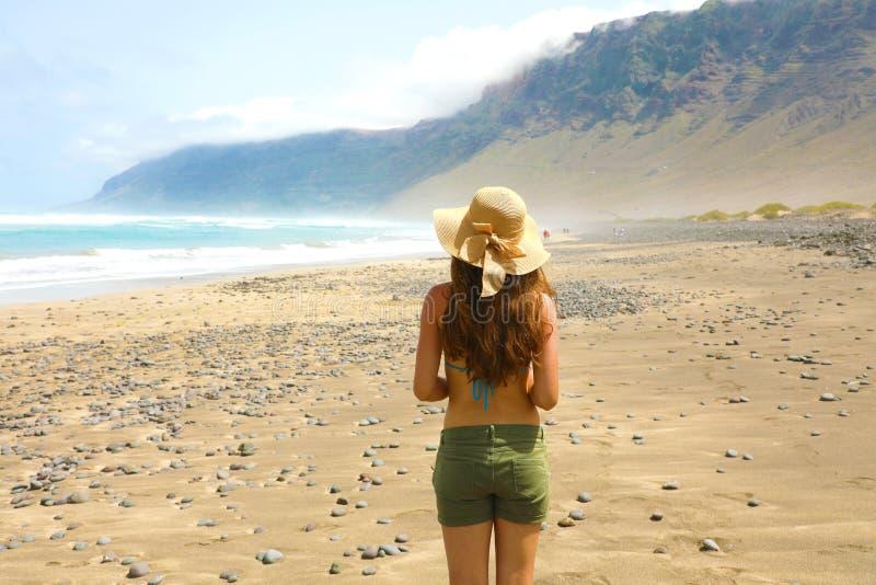 Belle fille avec le chapeau regardant au paysage suggestif de Caleta Famara, Lanzarote, Îles Canaries image libre de droits