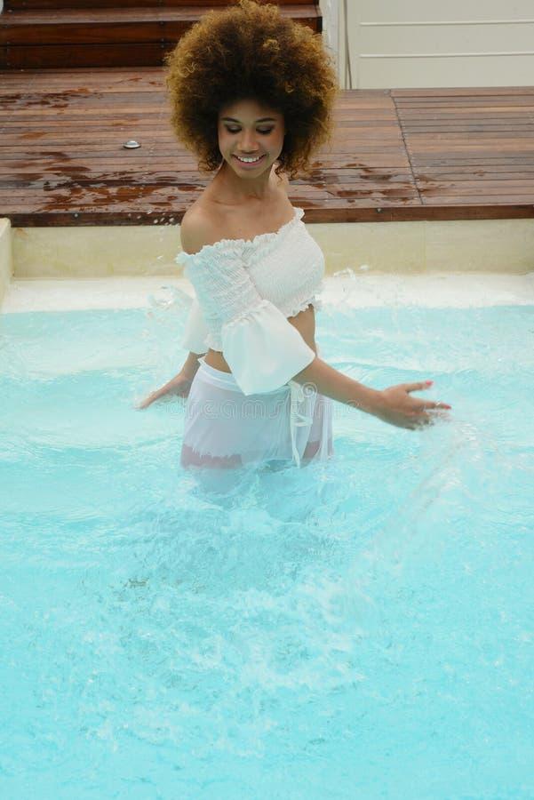 Belle fille avec le jeu mince de corps avec de l'eau dans la piscine de station thermale photo libre de droits