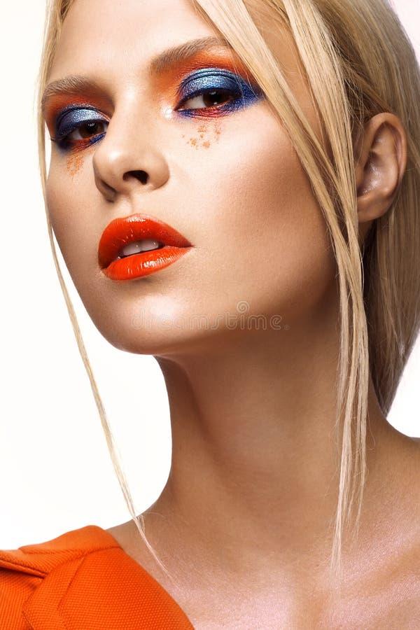 Belle fille avec le maquillage coloré lumineux et les lèvres oranges Visage de beauté photographie stock libre de droits