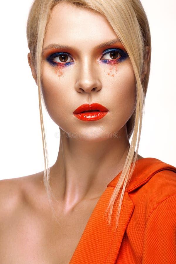 Belle fille avec le maquillage coloré lumineux et les lèvres oranges Visage de beauté image stock