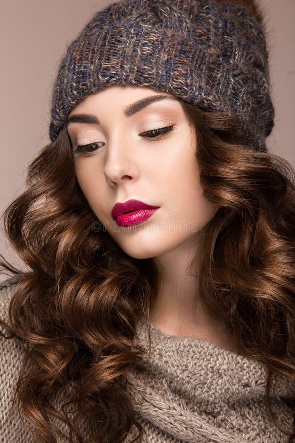 Belle fille avec le maquillage doux, boucles dans le chapeau brun de knit Image chaude d'hiver Visage de beauté photos stock