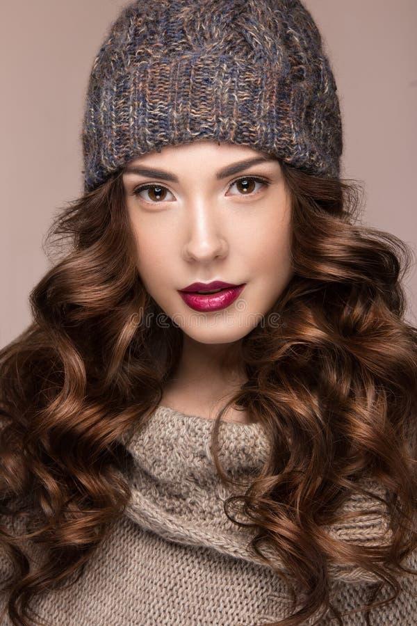 Belle fille avec le maquillage doux, boucles dans le chapeau brun de knit Image chaude d'hiver Visage de beauté images libres de droits