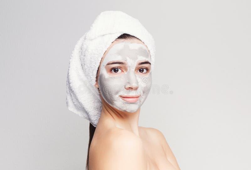 Belle fille avec le masque appliqué d'argile au fond blanc images libres de droits