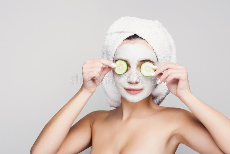 Belle fille avec le masque appliqué d'argile au fond blanc photos libres de droits