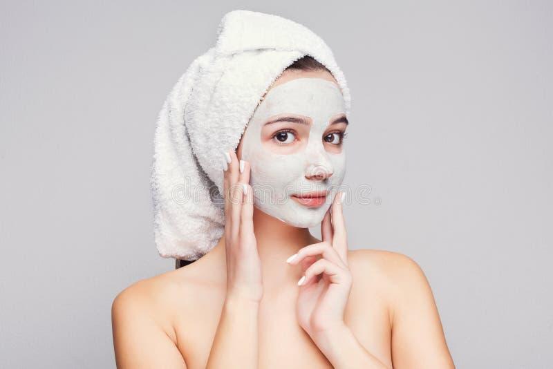 Belle fille avec le masque appliqué d'argile au fond blanc photo stock
