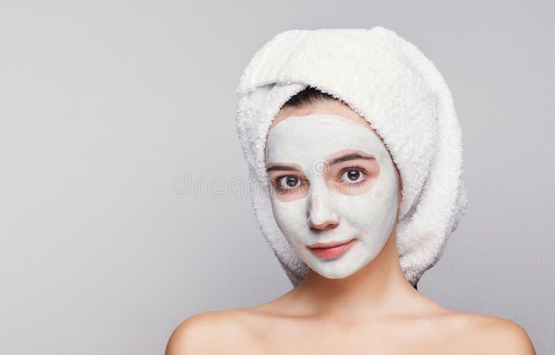 Belle fille avec le masque appliqué d'argile au fond blanc image libre de droits