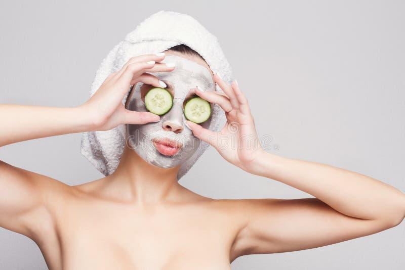 Belle fille avec le masque appliqué d'argile au fond gris photographie stock