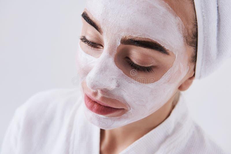 Belle fille avec le masque cosmétique sur son visage d'isolement sur le fond blanc photographie stock libre de droits