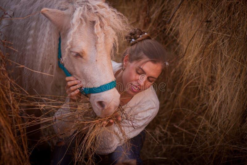 belle fille avec le poney blanc de crinière photos stock