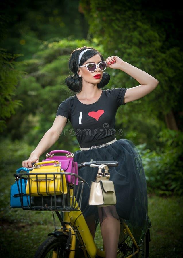 Belle fille avec le rétro sembler utilisant un équipement noir ayant l'amusement dans le parc avec la bicyclette Concept extérieu photo stock