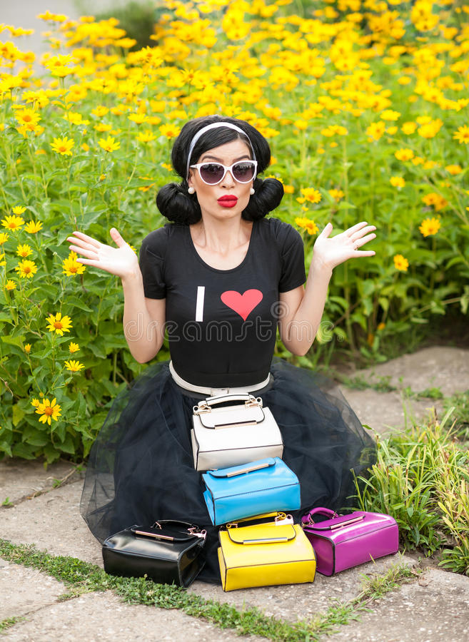 Belle fille avec le rétro sembler utilisant un équipement noir ayant l'amusement dans le parc montrant beaucoup de sacs colorés B image stock