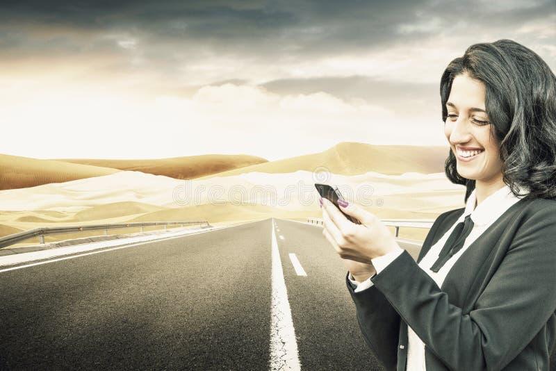 Belle fille avec le smartphone dans une route de désert image libre de droits
